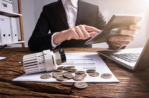 Berechnung von Heizkosten mit Taschenrechner und Laptop