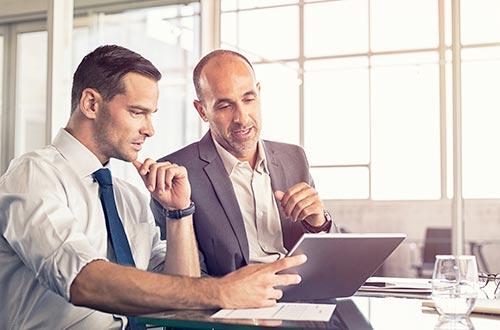 Zwei Geschäftsmänner in der Besprechung mit einem Laptop
